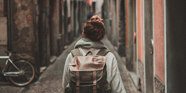 young person with backpack walking in a cobblestone alley